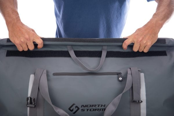 Showing the second step on how to roll the top closed of the 60 litre north storm roll top waterproof duffel bag. Shows two hands rolling the top of the bag in a downwards motion