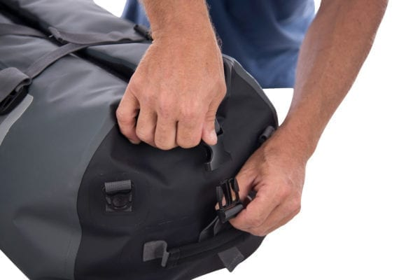 Showing the final step on how to clip close the top of the 60 litre north storm roll top waterproof duffel bag. Shows two hands clipping the fastener together down the side of the duffel bag