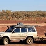 Woolgoolga offroad's 4 wheel drive parked on very red australian dirt. The 4x4 has a North Storm 60 litre waterproof and dust proof bag tied on the roof racks